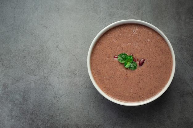 Gorąca zupa z czerwonej fasoli w białej misce na ciemnej podłodze