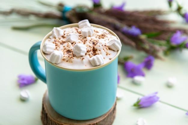 Gorące cappuccino z piankami i pianką w jasnoniebieskiej filiżance z kwiatami.
