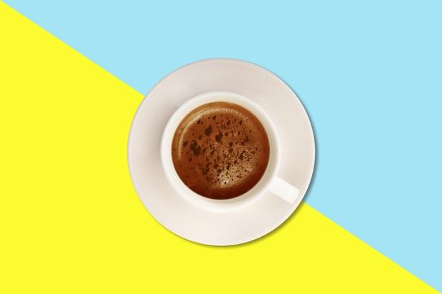 Gorące cappuccino z prostą pianką na filiżance biały na białym tle na kolorowym tle.