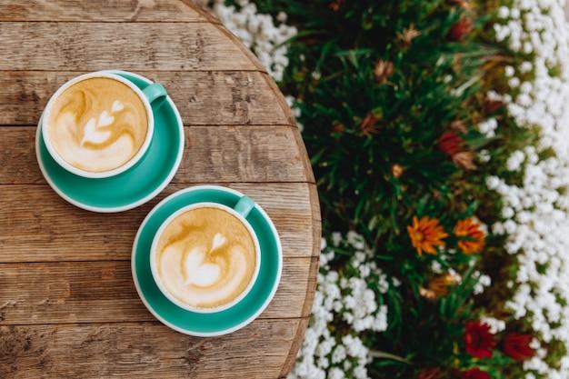 Gorące cappuccino ze sztuką latte na drewnianym stole z tarasem