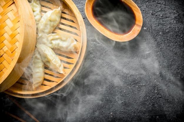 Gorące chińskie tradycyjne pierożki gedza w bambusowym parowcu z sosem sojowym na rustykalnym stole.