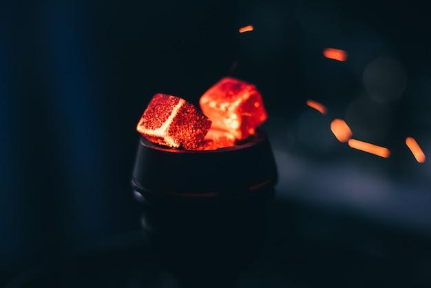 Gorące czerwone węgle na fajki wodne z iskrami na ciemnym tle