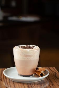 Gorące kakao na drewnianym stole zbliżenie z miejsca na kopię na ciemnym tle.