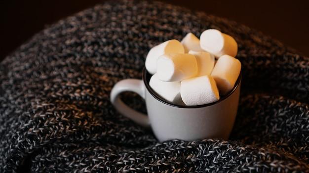 Gorące kakao z pianką w białym ceramicznym kubku. koncepcja przytulnych wakacji i nowego roku.