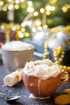 Gorące kakao z piankami, śmietaną i ciasteczkami na świątecznym tle bożego narodzenia