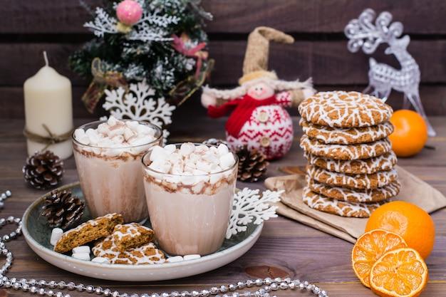 Gorące kakao z piankami w okularach i ciasteczka świąteczne na drewnianym stole z ozdób choinkowych