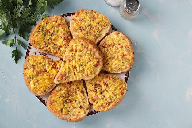 Gorące kanapki z serem i kiełbasą w talerzu na bławym tle