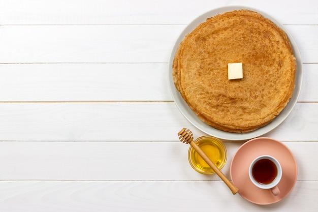 Gorące naleśniki z masłem i miodem na talerzu. śniadanie z herbaty i krepy widok z góry z copyspace.