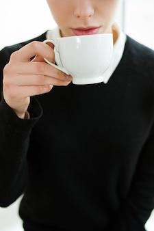 Gorące napoje kawa herbata koncepcja kakao. kobieta pije napój z białego kubka.