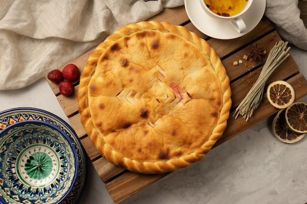 Gorące osetyjskie słodkie ciasto z nadzieniem truskawkowym obok ozdobnych narodowych uzbeckich naczyń ceramicznych o tradycyjnym wzorze.