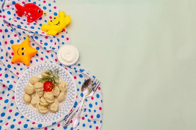 Gorące pierożki mięsne ze świeżą śmietaną. domowe zdrowe jedzenie dla dzieci, śmieszne zabawki