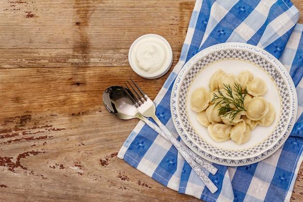 Gorące pierożki mięsne ze świeżą śmietaną. tradycyjne rosyjskie pelmeni, ravioli, warzywa