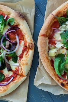 Gorące pyszne pizze, widok z góry. pepperoni na drewnianym stole. smaczne włoskie jedzenie.