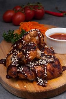 Gorące skrzydełka z kurczaka z sosem pomidorowym na drewnianej desce