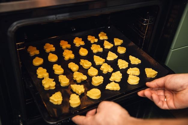 Gorące, słodkie, żółte ciasteczka w piekarniku. człowiek posiada tacę