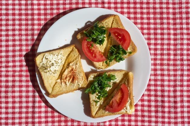 Gorące świeże tosty z serem i pomidorem na talerzu, płaski widok