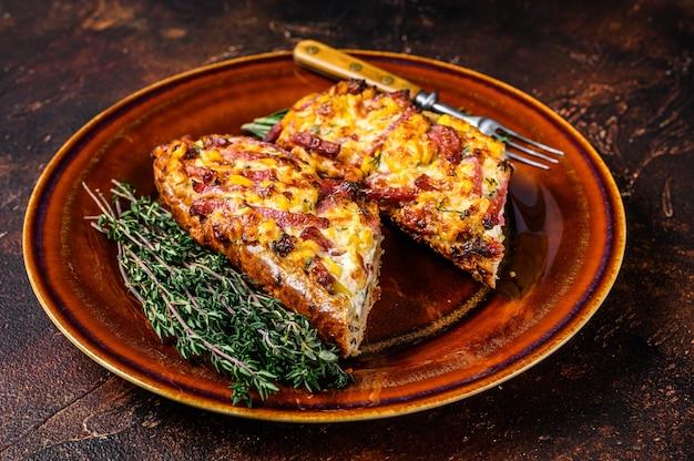 Gorąco pieczona kanapka na chlebie bagietkowym z szynką, boczkiem, warzywami i serem na rustykalnym talerzu