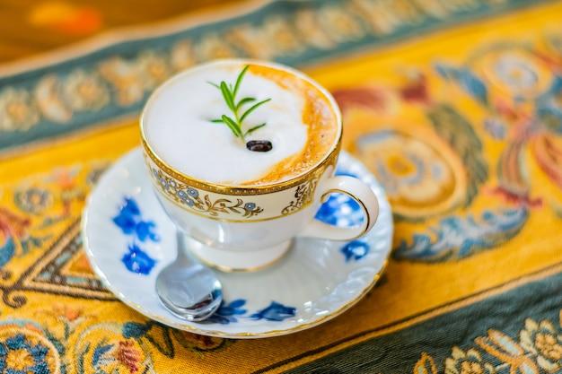Gorący cappuccino w białej ceramicznej filiżance na luksusowym stołowym płótnie i drewnianym stole, odgórny widok