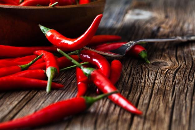 Gorący chili pieprz na rocznika srebra rozwidleniu nad drewnianym tłem