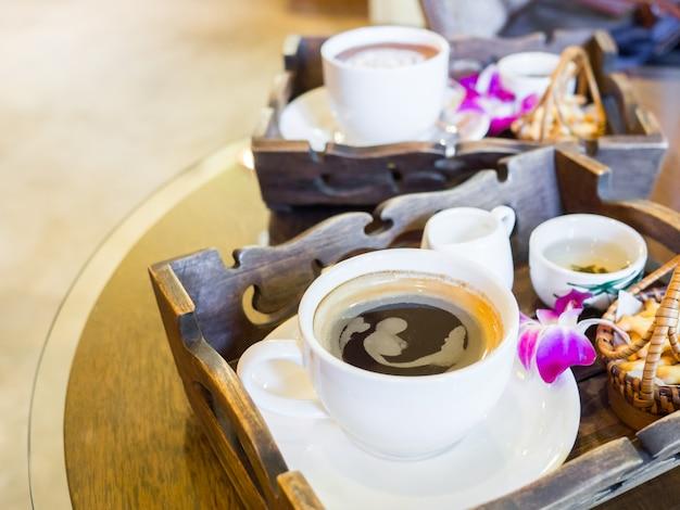 Gorący czarny zestaw do kawy z ciasteczkami i storczykami ozdobionymi na stole