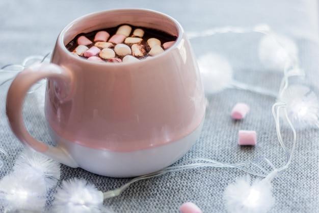 Gorący czekoladowy różowy kubek ceramiczny marshmallows i girlanda na szarym tle z dzianiny