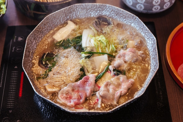 Gorący i gotujący się bulion shabu z kapustą, wieprzowiną eryngii, enotitake, tofu i kurobuta.