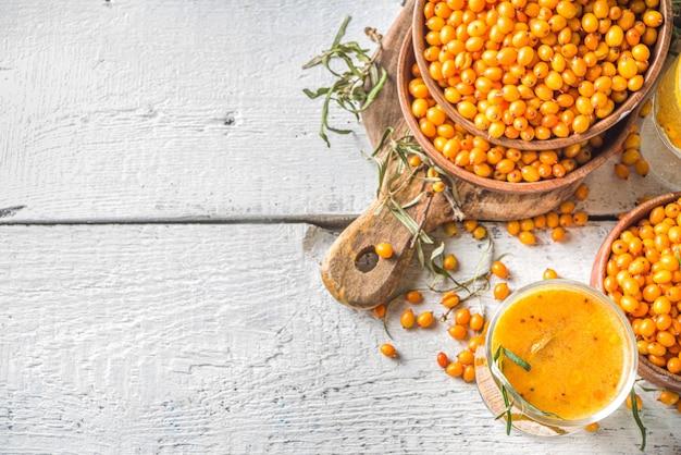 Gorący jesienny napój organiczny. zdrowy napój dietetyczny, żywność niszcząca odporność. herbata rokitnikowa z pomarańczą i miodem w szklanych filiżankach. białe tło kopii przestrzeni