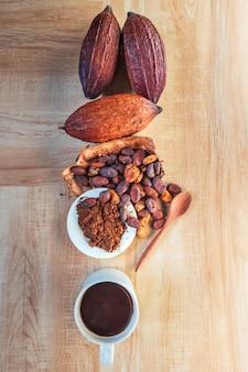 Gorący kubek kakaowy z proszkiem kakaowym i ziarnami kakaowymi na drewnianym tle
