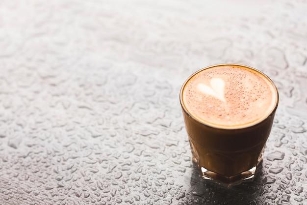 Gorący latte z kształtem serca w szkle na powierzchni kropli wody