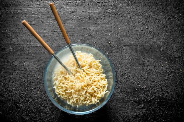 Gorący makaron instant w misce z pałeczkami na czarnym rustykalnym stole.