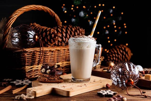 Gorący napój czekoladowy z bitą śmietaną. przytulny świąteczny skład na ciemnym tle drewniane. słodkie przysmaki na chłodne zimowe dni.