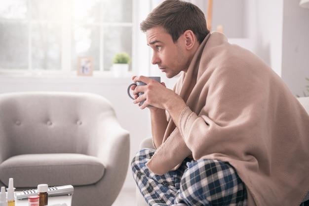 Gorący napój. miły młody człowiek pije filiżankę gorącej herbaty będąc chory