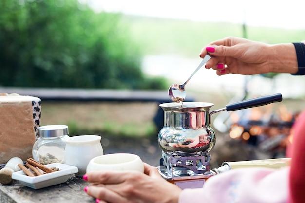 Gorący napój na naturze. proces gotowania kawy z przyprawami w naturze.