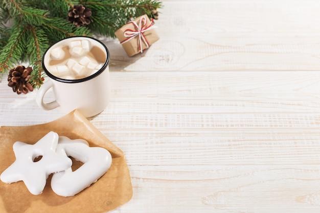 Gorący napój świąteczny z piankami w żelaznym kubku i piernikowymi ciasteczkami na białym stole. , wakacje, copyspace.