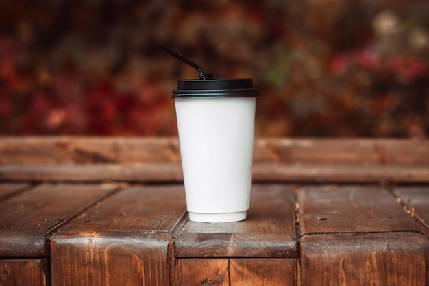 Gorący napój w białym papierowym kubku ze słomką na drewnianej ławce. słoneczny jesienny dzień. makieta do projektowania