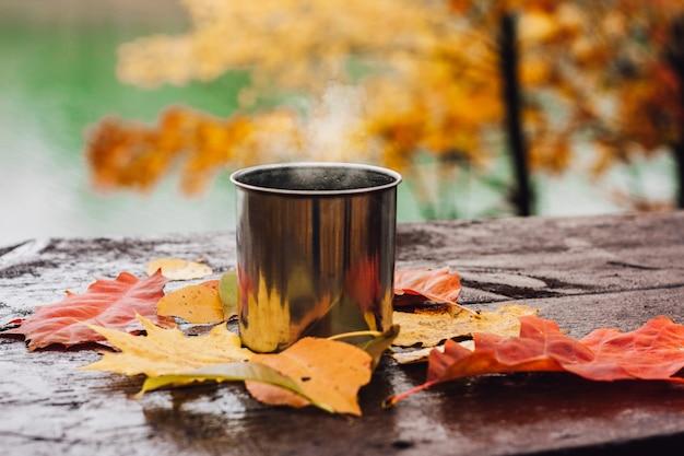 Gorący napój w stalowym kubku na drewnianym stole.