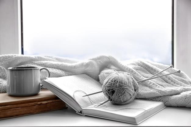 Gorący napój z książkami, nitkami i kratą na parapecie