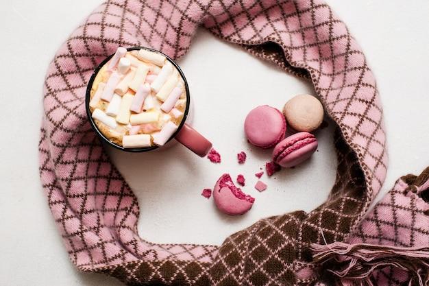 Gorący napój z pianką i kolorowymi cukierkami z kraciastym szalikiem dookoła