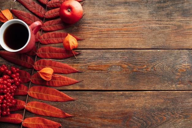 Gorący napój zapewniający ciepło jesienią. koncepcja czarnej kawy lub herbaty. spadek liści ściany