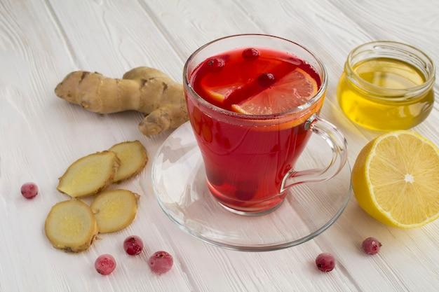 Gorący napój żurawinowy z cytryną i imbirem w szklanym kubku na białym drewnianym stole. zdrowy napój medyczny.