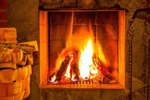 Gorący ogień w kominku. wiązka drewna opałowego w koszu