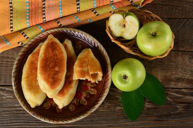 Gorący pasztecik ze świeżymi zielonymi jabłkami na drewnianym tle