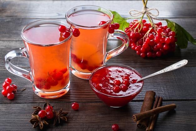 Gorący pikantny napój z kaliną w szklanych filiżankach ze świeżymi jagodami kaliny na stole kuchennym dsrk.
