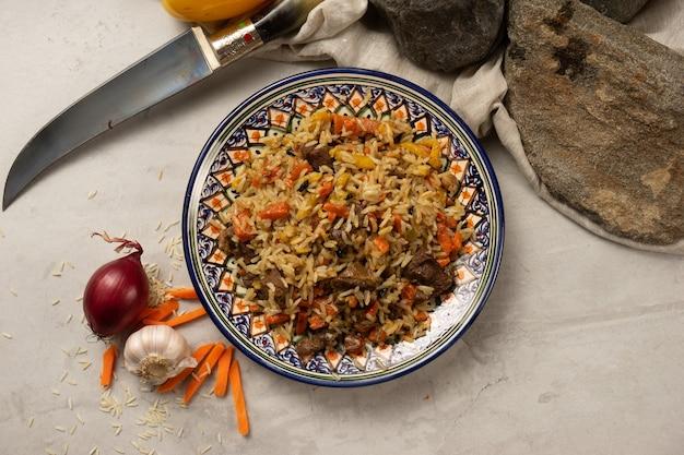 Gorący pilaw z jagnięciną lub wołowiną na ozdobnym, narodowym talerzu uzbeckim z tradycyjnym wzorem.