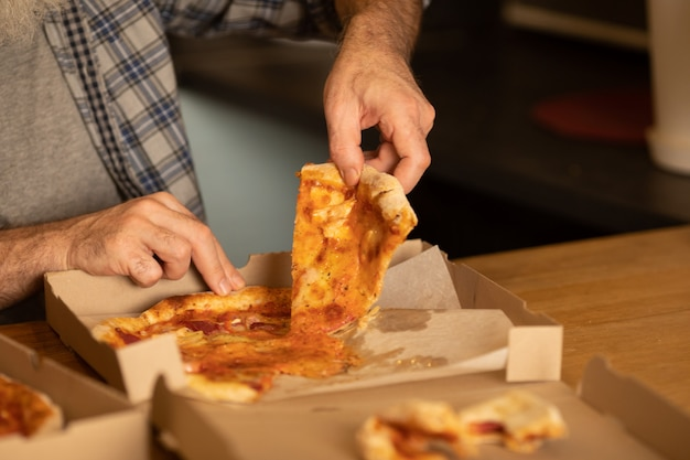 Gorący plasterek pizzy z topliwym serem. lunchu lub kolacji pyszne włoskie jedzenie tradycyjne na drewnianym stole w widoku z boku. selektywne ustawianie ostrości.