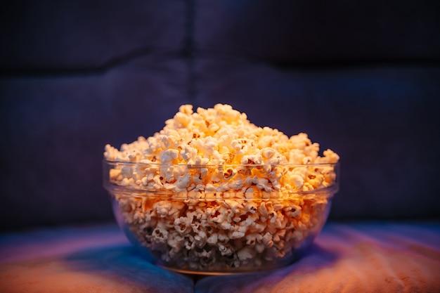 Gorący popcorn w misce na kanapie czeka na oglądanie telewizji