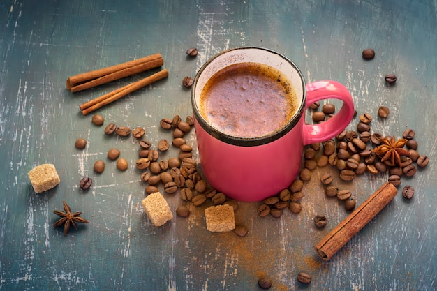 Gorący różowy kubek kawy z cynamonem na starym ciemnym tle.