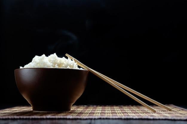 Gorący ryż w brązowej misce pałeczkami w stylu japońskim