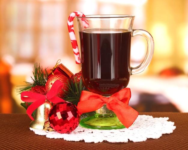 Gorący smaczny napój ze świątecznymi cukierkami i innymi dekoracjami na jasnym tle