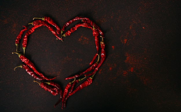 Gorący suchy czerwony pieprz na czarnym tle. serce papryczki chilli.